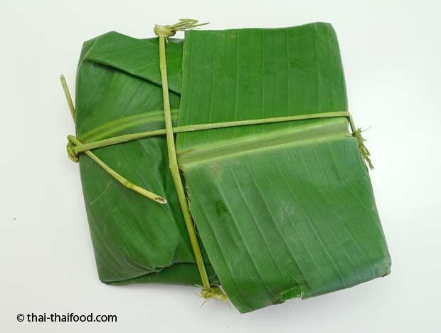 grüner Reis verpackt in Bananenblätter