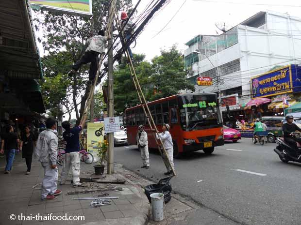Stromleitungen werden unter Zuhilfenahme einer Bambusleiter verlegt