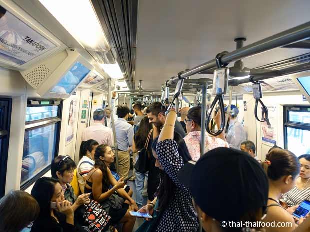 Sitzen und stehen im Skytrain von Bangkok