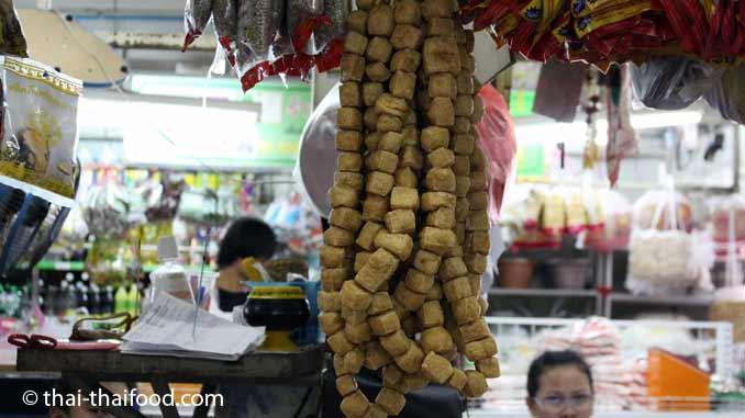 Tofu Stücke aufgereiht auf einer Schnur
